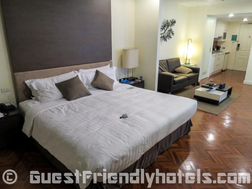 Beig bed at on one end of my room inside Phachara Suites Sukhumvit