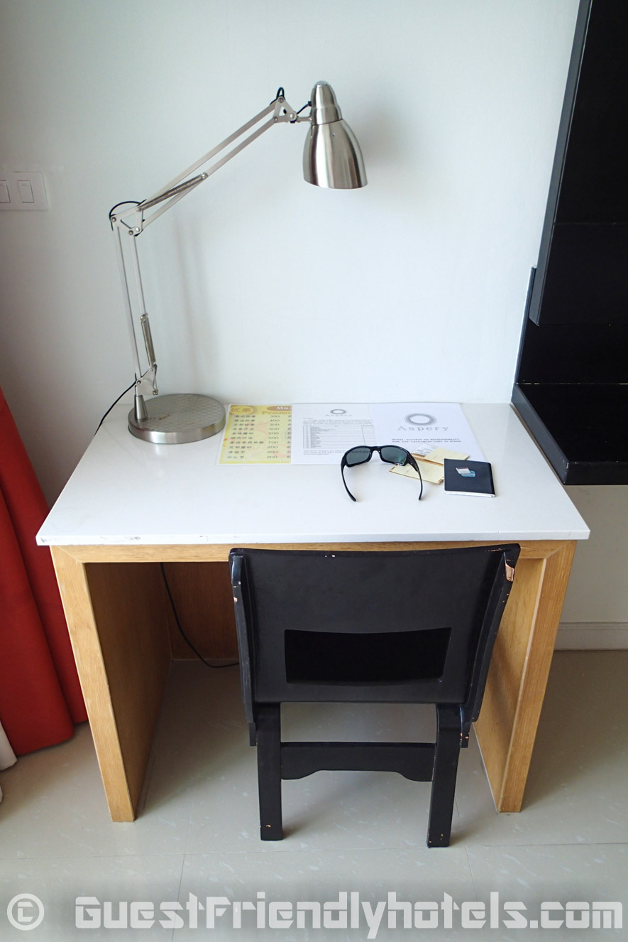 Small desk and chair next to the TV in Aspery Hotel room