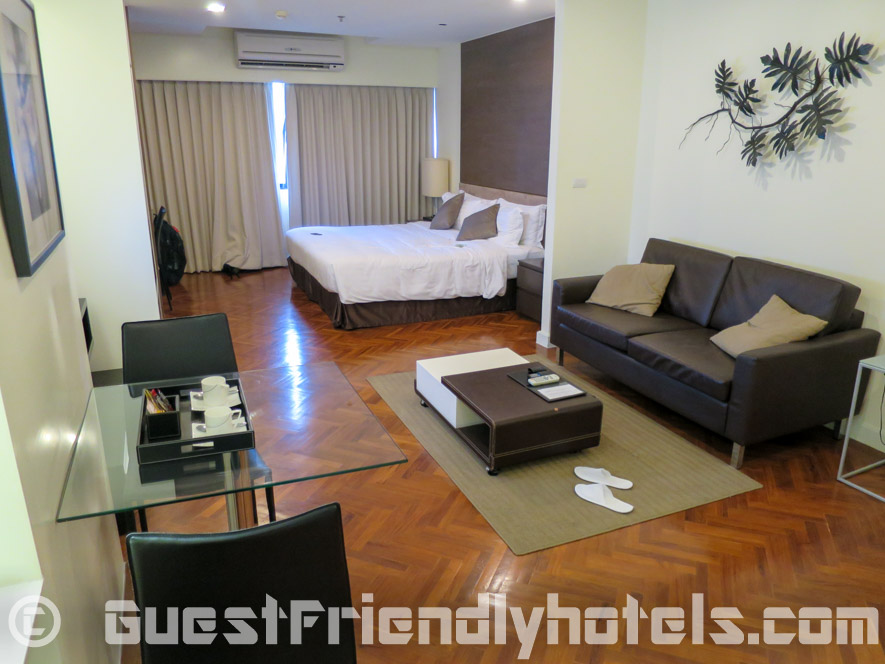 Small dining table with living room and bed in the back at Phachara Suites