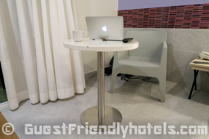 Small table with a plastic chair is found next to the balcony and bed in deluxe rooms of the Grand Bella Hotel Pattaya
