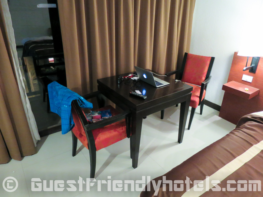 Table ans chairs next to the bed and balcony inside rooms of Patong Bay Garden Resort