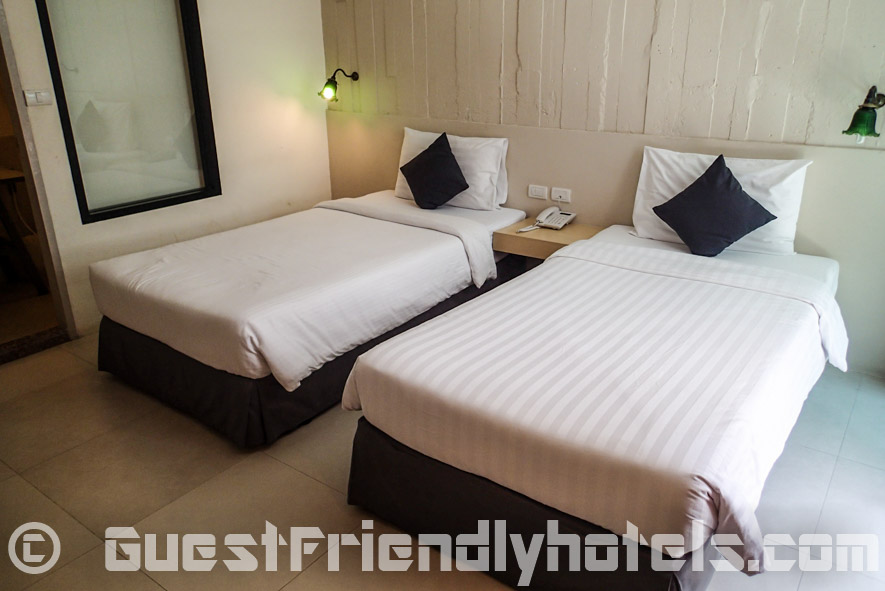 Twin beds at Acca Patong with toilet in the back